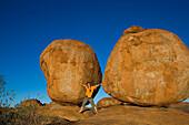Woman standing inbetween two of the round red rocks called Devils Marbles and pretending to hold them, Devils Marbles Conservation Reserve, near Wauchope, Northern Territory, Australia