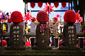 Three stone figures with knitted red caps in Shiba Park, Tokyo, Kanto Region, Honshu, Japan