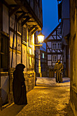 Two people wearing traditional coats meet under a street lamp in a small alley called Paradiesgasse with half-timbered houses at dusk, Bad Wildungen, Hesse, Germany, Europe