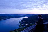 A couple admires Lake Edersee in Kellerwald-Edersee National Park from Waldeck Castle at dusk, Lake Edersee, Hesse, Germany, Europe