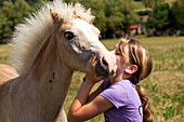 Young girl giving a young foul a kiss, Wellen, Hesse, Germany, Europe