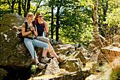 Two women resting along the Kellerwaldsteig hiking track at Wuestegarten in the Kellerwald forest in Kellerwald-Edersee National Park, Kellerwald, Hesse, Germany, Europe