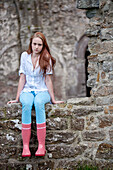 Red haired teenage girl wearing wellington boots with red dots sitting on a stone wall, Clonmacnoise, County Offaly, Ireland, Europe