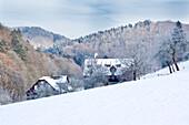 Idyllic winter scene with Kuchenmuehle watermill in the snow in Lengeltal valley in Kellerwald-Edersee National Park, Frankenau, Hesse, Germany, Europe