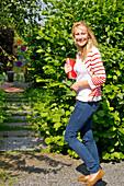 A young blond woman gesturing to follow her through the Kurpark Bad Wildungen, Bad Wildungen, Hesse, Germany, Europe
