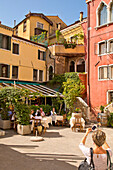 Woman taking a photograph of houses and a cafe with her smartphone, Venice, Veneto, Italy, Europe