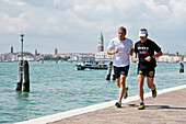 Two men jogging along the waterfront near the Biennale grounds, Venice, Veneto, Italy, Europe