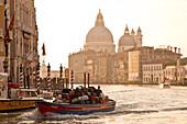 Boat transporting luggage on the Grand Canal in front of Chiesa di Santa Maria della Salute church at sunrise, Venice, Veneto, Italy, Europe