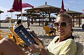 Woman relaxing on the beach, Tel-Aviv, Israel, Asia