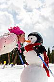Girl kissing a snowman, Kreischberg, Murau, Styria, Austria