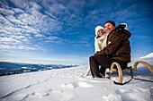 Couple sitting on a sledge in snow, Muehlen, Styria, Austria