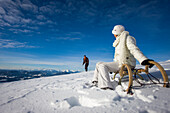 Couple with sledge in snow, Muehlen, Styria, Austria