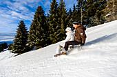 Couple downhill tobogganing, Muehlen, Styria, Austria