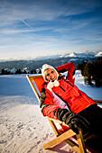 Young woman sunbathing, Kreischberg, Murau, Styria, Austria
