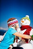 Girl and a snowman, Frauenalpe, Murau, Styria, Austria