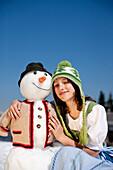 Girl wearing a dirndl beside a snowman, Frauenalpe, Murau, Styria, Austria