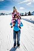 Woman giving girl a piggyback ride, Planai, Schladming, Styria, Austria