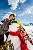 Two children posing with a snowman, Planai, Schladming, Styria, Austria