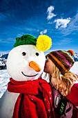 Girl kissing a snowman, Planai, Schladming, Styria, Austria