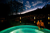 Couple sitting on thermal pool edge, Bad Radkersburg, Styria, Austria