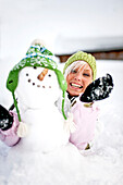 Young woman building a snowman