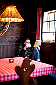 Woman drinking a cup of tea while reading a book, Styria, Austria