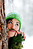 Young woman with a fake beard behind a tree