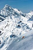 Skier downhill skiing in deep snow, Alagna Valsesia, Piedmont, Italy
