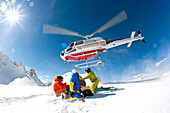 Heliskiers crouching in snow, helicopter flying off, Puma Lodge, Araucania Region, Chile