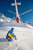 Heliskier crouching in snow, helicopter flying off, Puma Lodge, Araucania Region, Chile
