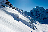 Skier downhill skiing in deep snow, Gran Zebru, Sulden, Ortler Alps, South Tyroll, Italy