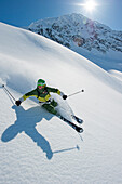 Skier downhill skiing in deep snow, Chugach Powder Guides, Girdwood, Alaska, USA