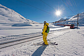 Skier beside railroad tracks, Diavolezza, Engadin, Canton of Graubuenden, Switzerland