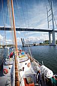 Sailing ship entering harbor, Rugia Bridge and Rugia Causeway in background, Stralsund, Mecklenburg-Western Pomerania, Germany