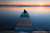 Men at Trasimeno lake's shores in the sunset lights, Umbria
