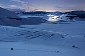 A plain covered of snow, in a wintertime night, with the little village of Castelluccio di Norcia in the background, Umbria