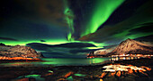 Aurora borealis reflected in the sea, with clouds seen from a fjord, green sky with big mountain in background