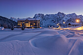 An health institution on Misurina's lake in wintertime's sunset, with peaks in the background, Dolomites, Italy