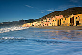 Sunrise in the fisherman village near at the sea in Varigotti town, La Spezia, Liguria, Italy. Beautiful vision of the waves near the house in the beach