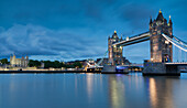 The Tower Bridge and the Tower of London are reflected in the calm waters of the Thames in the early evening lights.