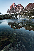 Sunrise in Monviso Mountains reflected in the trasparent water of Superior Lake, Crissolo, Cuneo, Italy