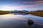 Colorful sunrise reflecting in a seasonal puddle at the foot of Mount Tonale, on the border between Lombardy and Trentino Alto Adige , South Tyrol. The group of Mount Presanella in the background, Italy