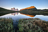 Lake Baste at sunrise reflecting the massive mount Pelmo, Zoldo group, Dolomites of Belluno, province of Belluno, Trentino Alto-Adige, Italy.