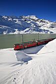 The Bernina Express , Unesco World Heritage at the Bernina pass close to Lake Bianco, Bernina pass, Alps, Engadin, Canton Graubuenden, Switzerland.