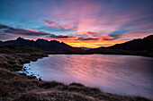 Amazing sunrise coloring the whole sky while the wind gently moves the surface of Lake Arcoglio, Valmalenco, Sondrio, Lombardy, Italy