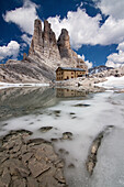 Little alpine lake, in the beginning of summertime, with a refuge and wonderful towers of dolomite, Dolomites
