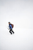 Young woman, Jess Meiris, carries snowboard under arm while hiking up Mt. Hood in the Oregon Cascades.