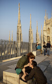 A couple kiss on the roof of Milan's Duomo.
