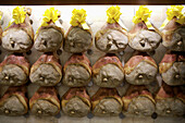 Legs of prosciutto line the walls at the food store Peck in Milan