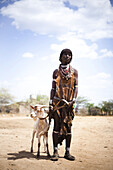 HAMER VILLAGE, OMO VALLEY, ETHIOPIA. A portrait of a woman standing next to her goat. She is dressed in traditional clothes of the Hamer people.